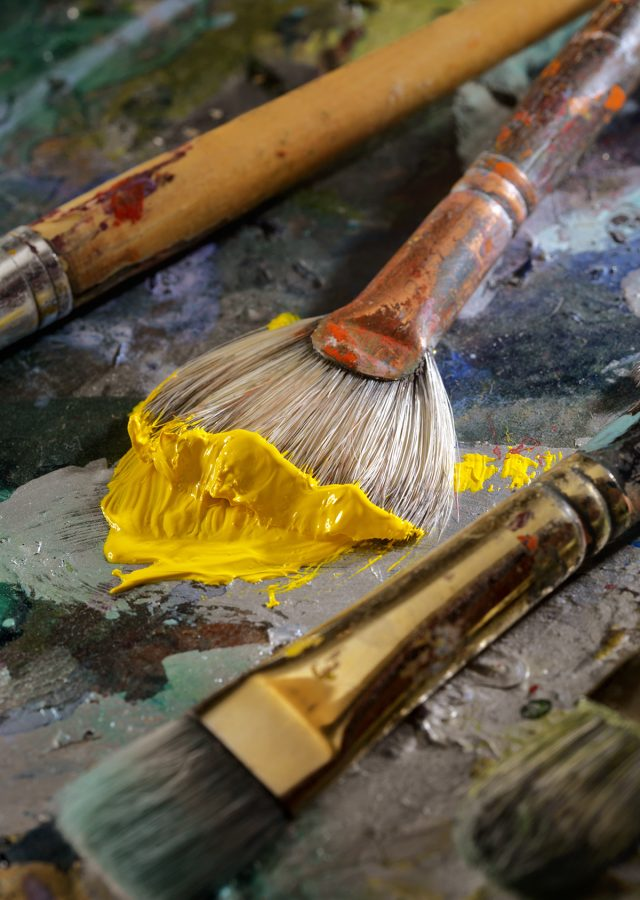 Closeup of paint brushes and wet paint on an artist's palette
