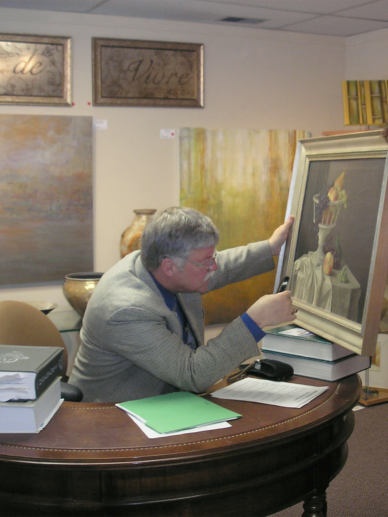 Broadway Galleries guest appraiser inspecting a painting